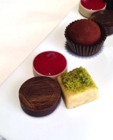 Petit Four, Truffle with tiramisu, chocolate with hazelnut ganache, white chocolate and pistachio, chocolate basket with a liquid gelatin of raspberry.